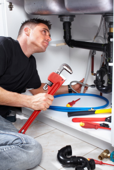 Garland plumber prepares to fix sink drain with a pipe wrench in hand